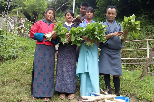 Students in Bhutan with a freshly picked crop of nutritious leafy vegetables. Photo by Choki Gyeltshen